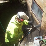 Egress window opening being cut with a cement chain saw.