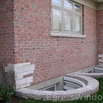 IRC code compliant, two basement egress wells installed and adorned with landscaping stone