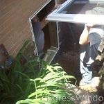 In-swing vinyl windows for basement egress being installed.