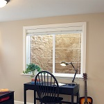 Egress window kit seen outside of a light-filled basement home office.