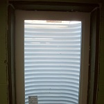 Egress basement window installed with accompanying steel window well.